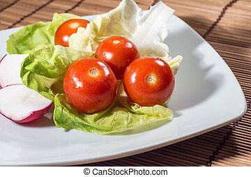 Fresh vegetable dish with tomatoes and radishes on plate