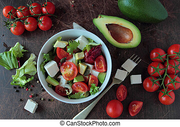 Fresh vegetable salad in a bowl on wooden board