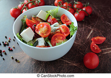 Fresh vegetable salad in a bowl on wooden kitchen table