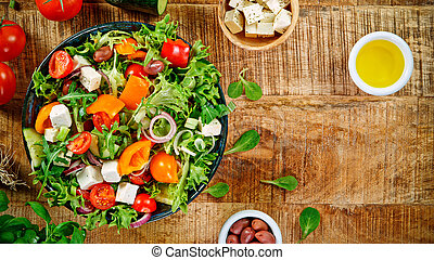 Fresh vegetable salad on vintage wooden table, top view.