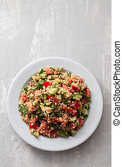 fresh vegetable salad with couscous on white plate