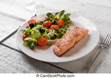 fresh vegetable salad with grilled salmon on dish
