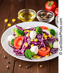 Fresh vegetable salad with mozzarella on wooden table.