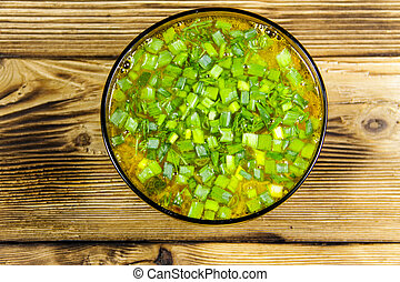 Fresh vegetable soup in glass bowl on wooden table. Top view