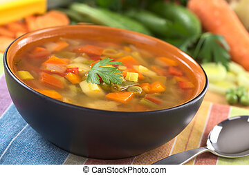 Fresh vegetable soup made of green bean, pea, carrot, potato, red bell pepper, tomato and leek in black bowl garnished with a parsley leaf with ingredients in the back (Selective Focus, Focus on the f