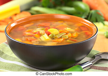 Fresh vegetable soup made of green bean, pea, carrot, potato, red bell pepper, tomato and leek in black bowl with ingredients in the back (Selective Focus, Focus on the vegetables in the middle of the