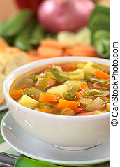 Fresh vegetable soup made of green bean, pea, carrot, potato, red bell pepper, tomato and leek in white bowl with baguette slices and ingredients in the back (Selective Focus, Focus on the vegetables