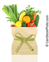 Fresh vegetables and fruits in a paper grocery bag with measuring tape