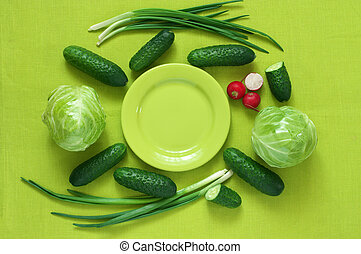 Fresh vegetables and plate on green