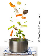 Fresh vegetables falling into a pot isolated on a white background