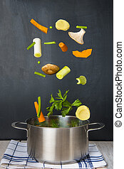 Fresh vegetables falling into a pot with a black  background