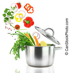 Fresh vegetables falling into a stainless steel casserole ...