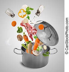 Fresh vegetables falling into stainless steel pot.