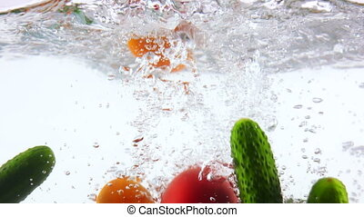 Fresh vegetables falling into water with splashes in slow motion