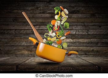 Fresh vegetables flying into a pot