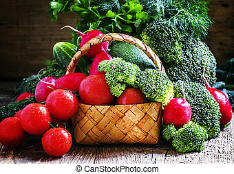 Fresh vegetables in a wicker basket: tomatoes, broccoli, cucumber, avocado, radishes, parsley, dill, vintage wooden background, selective focus