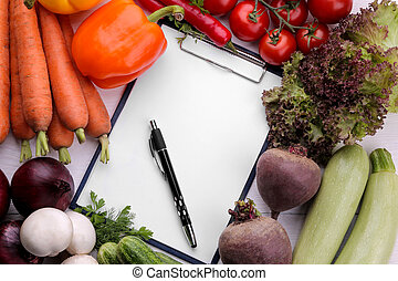 Fresh vegetables including lettuce leaves onion pepper beetroot carrots zucchini and tomatoes with a blank for recipes or for writing