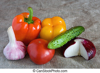 Fresh vegetables lie on linen cloth.