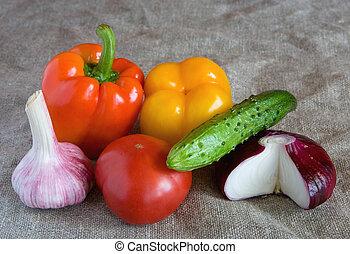 Fresh vegetables lie on linen cloth.