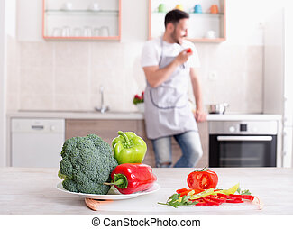 Fresh vegetables on table with man cooking in background