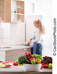 Fresh vegetables on table with woman in background