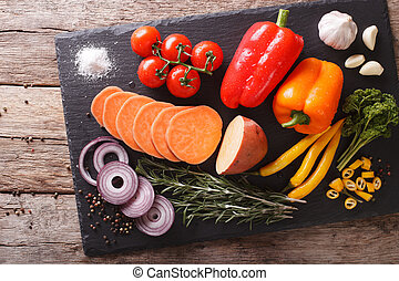 Fresh vegetables sweet potatoes, peppers, tomatoes, onions, garlic, rosemary and spices closeup. Horizontal top view