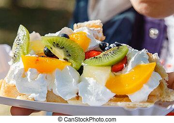 Fresh waffle cake with fruit and whipped cream close-up.