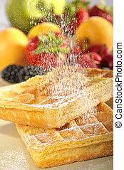 fresh waffles with icing sugar and fruits