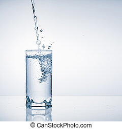 Fresh water pouring into glass on blue background