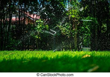 fresh water splash from the sprinkle pole settle in the grass feild in the outdoor garden.