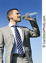 fresh water - businessman in suit is drinking fresh water in...