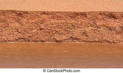Fresh water stream flowing across sand surface on the beach