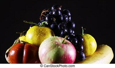 Fresh wet fruit rotating over black - Fresh fruit and water...
