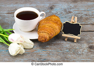 Fresh white tulip and coffee cup with croissant with blackboard with empty space for a text over wooden background