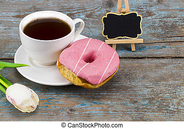 Fresh white tulip and coffee cup with donut with blackboard with empty space for a text over wooden background
