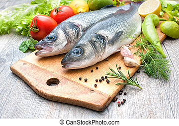 Fresh whole sea basses a cutting board