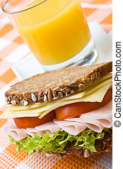 Fresh wholemeal cheese and ham sandwich with orange juice