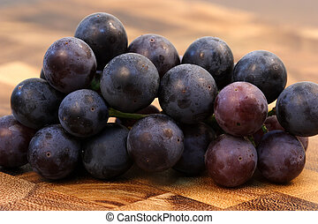 fresh wine grapes - grapes on fine wood cutting board with...
