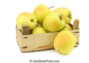 fresh yellow apples and a cut one in a wooden crate