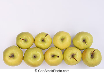 Fresh yellow apples with short brown cuttings lie in two rows at bottom of the white sheet, I cut the free space for the text.