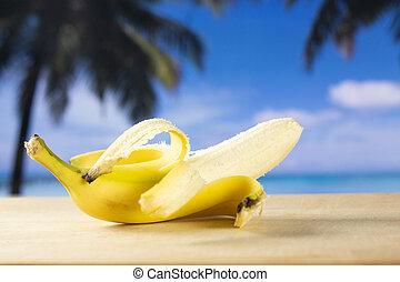 Fresh yellow banana with palm beach behind