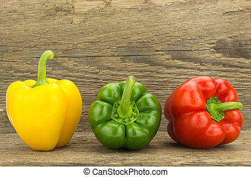 Fresh yellow, green and red bell peppers, on wooden surface.