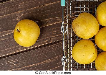 Fresh yellow plum on brown wood