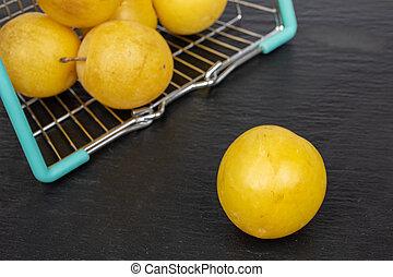 Fresh yellow plum on grey stone