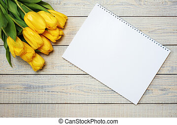 Fresh yellow tulips with easter greeting card on wooden background.
