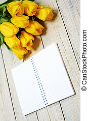 Fresh yellow tulips with empty open notepad on wooden background.