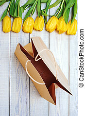 Fresh yellow tulips with empty paper bag on wooden background.