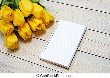 Fresh yellow tulips with greeting card on wooden background. Holiday background. Top view with copy space.