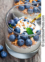 Fresh yogurt in a glass with whole flax and blueberries on wooden table