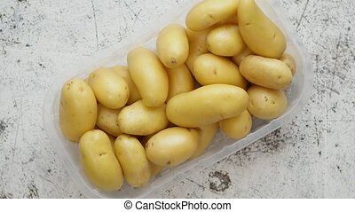 Fresh young potatoes in plastic basket placed on scatched ...